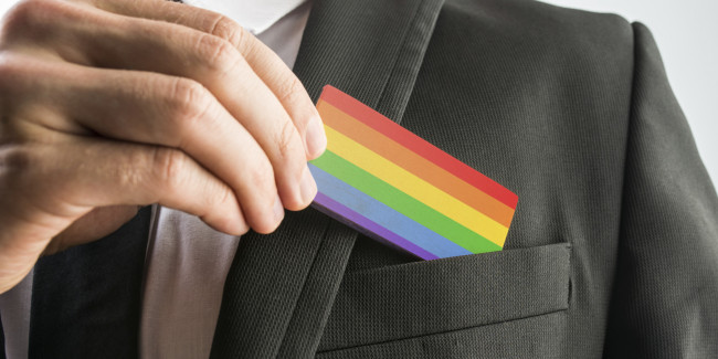 Man withdrawing rainbow flag business card. Image: stock photo.